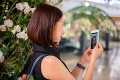 少妇在商城的用途手机 免版税库存图片