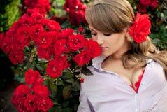少妇在嗅到红色玫瑰的花园里 免版税库存照片