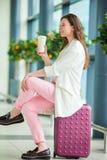 少妇在国际机场以她的去的行李和咖啡等待她的飞行 库存图片