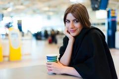 少妇在国际机场,饮用的咖啡 库存图片