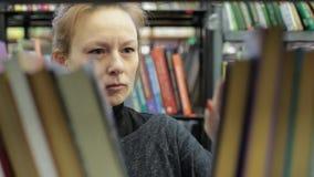 少妇在图书馆里选择一本书 她是在书之间的走廊 股票录像