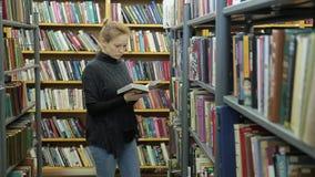 少妇在图书馆里选择一本书 她是在书之间的走廊 影视素材