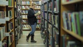 少妇在图书馆里选择一本书 她是在书之间的走廊 股票视频