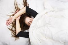 少妇在她的与闭合的眼睛的床上在,微笑在她的毯子下在安宁的睡眠以后 免版税图库摄影