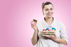 少妇在她的手和在桃红色背景隔绝的一块可口甜松饼杯形蛋糕上拿着篮子用复活节彩蛋 免版税库存照片