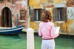 少妇在威尼斯,看地图的意大利 免版税图库摄影