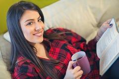 少妇在家坐放松在她的客厅的沙发 免版税库存图片