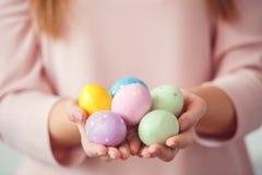 少妇在家复活节在拿着五颜六色的蛋特写镜头的兔宝宝耳朵的celbration概念 库存照片