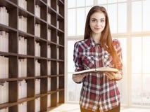 少妇在家庭书库里 免版税库存照片