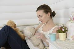 少妇在床上的儿童居室 免版税库存图片