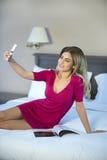 少妇在床上的采取一selfie 免版税图库摄影