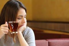 少妇在拿着一杯茶的咖啡店放松了 免版税库存图片