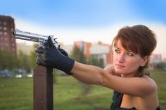 少妇在拿着枪的秋天公园 库存图片