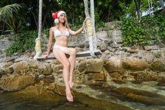 少妇在摇摆的圣诞老人帽子 庆祝新年在热的国家 免版税库存图片