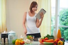 少妇在数字式片剂的食谱后 免版税图库摄影