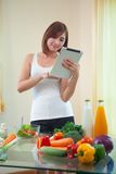 少妇在数字式片剂的食谱后 库存图片