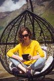 少妇在数字式设备的阅读书 片剂compuer 放松在休息室垂悬的椅子的行家女孩盘的腿 柳条swi 库存图片