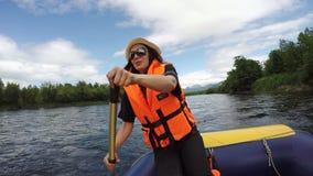 少妇在有效地荡桨在漂流的橙色救生衣穿戴了小船的桨 股票录像