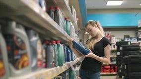 少妇在有机器油的瓶读标签在商店 影视素材