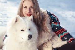 少妇在有狗的冬天公园 免版税库存图片