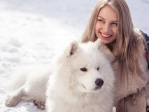 少妇在有狗的冬天公园 库存照片