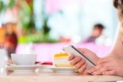 少妇在有电话发短信的冰淇凌店里 免版税图库摄影