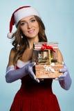 少妇在有礼物的圣诞老人衣裳 库存照片