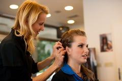 少妇在有美发师的交谊厅治疗和理发 库存照片