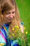 少妇在有花的草甸 图库摄影