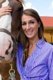 少妇在有马的槽枥在阳光下 免版税图库摄影