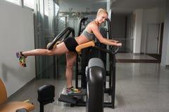 少妇在机器的锻炼腿 免版税库存照片