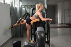 少妇在机器的锻炼腿 免版税库存图片