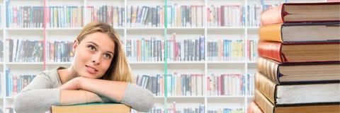 少妇在查寻的图书馆里和堆书 库存照片