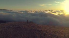 少妇在桃红色云彩上走到山高原边缘在日出 鸟瞰图 影视素材