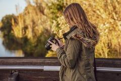 少妇在桥梁站立并且检查在照相机显示的图片预览 免版税图库摄影