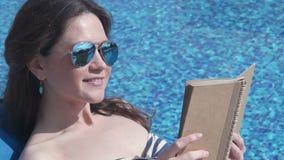 少妇在水池附近的阅读书,享受夏天阳光 影视素材
