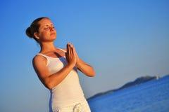 少妇在海滩的瑜伽凝思时 库存照片