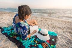 少妇在海滩读在泰国夏季 免版税库存照片