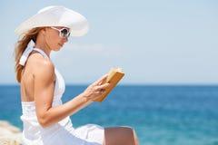 少妇在海滩的阅读书 免版税库存图片
