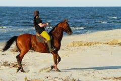 少妇在海滩的骑乘马 免版税库存照片