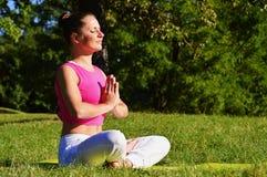少妇在瑜伽凝思时在公园 库存图片