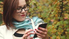 少妇在电话写消息在黄色叶子背景,当走在秋天公园时 股票录像