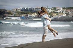 少妇在白色礼服观看的海在圣地与黑voncanic沙子,在有风beac的AzoresHappy年轻夫妇的米格尔海滩挥动 免版税库存照片