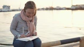 少妇在码头在春天晚上和图画附近坐由铅笔 股票录像