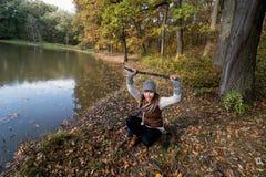 少妇在秋天之前取笑用木棍子在森林里 免版税库存图片