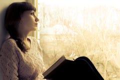少妇在窗口附近的阅读书。 免版税库存图片