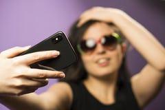 少妇在紫色背景做在太阳镜的Selfie 照片在最新的智能手机使用Google 库存照片