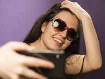 少妇在紫色背景做在太阳镜的Selfie 照片在最新的智能手机使用Google 免版税库存照片