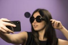 少妇在紫色背景做在黑老鼠太阳镜的Selfie 照片在最新的智能手机使用Google 免版税库存图片