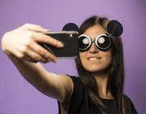 少妇在紫色背景做在黑老鼠太阳镜的Selfie 照片在最新的智能手机使用Google 免版税库存照片